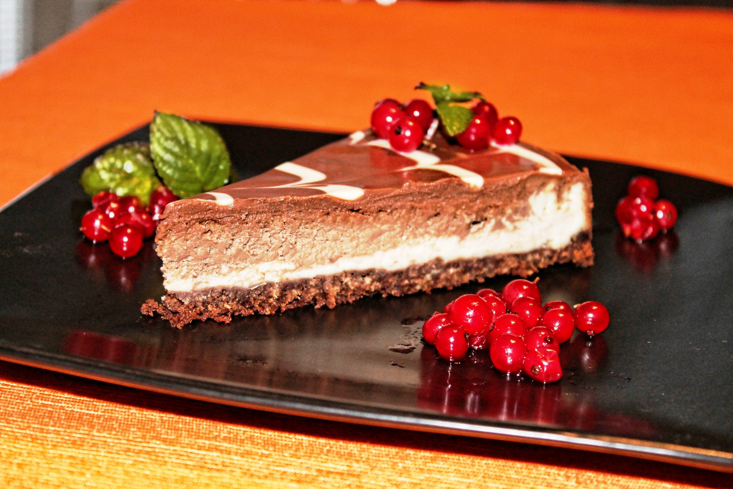 Fudge Cheesecake served on a black plate with current berries