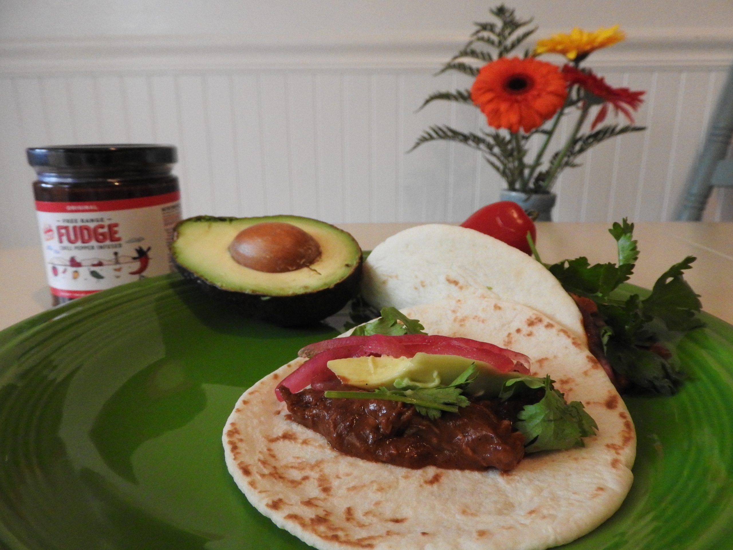 Decorative plate with sweet and spicy mole tacos for dinner. A jar of spicy hot fudge and flowers the back ground.