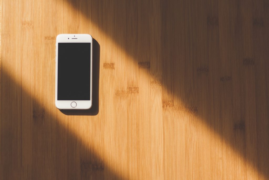 A white phone resting in a puddle of sunlight